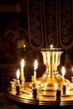 Velas y una lámpara que quema en la iglesia. Fotografía de archivo libre de regalías