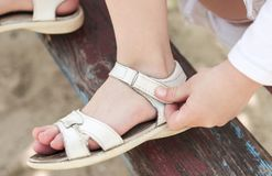 Velcro fastener on sandals. Children hands fasten sandals on their feet with the help of a velcro fastener royalty free stock photos