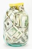 Vele 100 de dollarsbankbiljetten van de V.S. in een glaskruik Stock Foto
