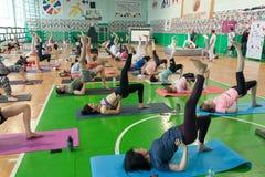 Vele actieve mensen die yogaasanas uitvoeren die samen, vóór Internationale yogadag opleiden royalty-vrije stock fotografie
