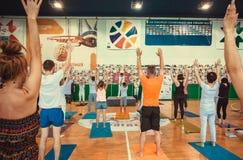 Vele actieve mensen met handen die op klasse steunen, die praktijk, asana op Internationale yogadag maken royalty-vrije stock fotografie