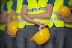 Vele arbeiders in vest met beschermende helm stock afbeelding