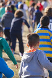 Vele atletische kinderen die op een zonnige dag lopen Openluchtkring Stock Afbeelding