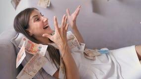 Vele bankbiljetten vliegen boven in de lucht in langzame motie Een meisje ligt en heel wat gelddalingen op haar de gelukkige vrou royalty-vrije stock afbeeldingen