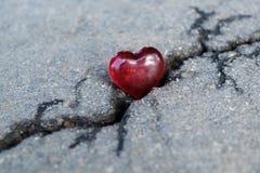 Vele barsten op het asfalt Op de grote barst ligt hart van glas royalty-vrije stock afbeelding