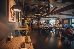 Vele bezoekers van restaurant met ontworpen binnenland in cultureel centrum Fotografiska Stock Afbeeldingen