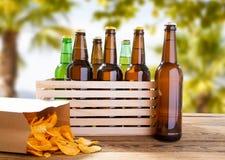 Vele bierflessen en pak spaanders op houten lijst aangaande vage tropische achtergrond stock afbeelding