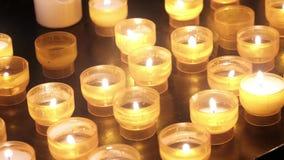 Vele brandende kaarsen in kerk leiden tot een geestelijk gevoel stock video