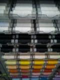 Vele draden van verschillende kleuren op plastic spoelen voor het naaien, voor handwerk stock fotografie