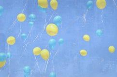 Vele gele en blauwe ballons die omhoog in de hemel vliegen Grungeachtergrond met ballons Vakantiegebeurtenis Royalty-vrije Stock Foto's