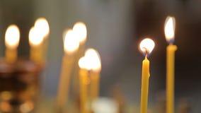 Vele gele kaarsen die branden in kerk? Sluit omhoog stock footage