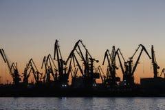 Vele grote kranen silhouetteren in de haven bij vroege ochtend, Se van Azov stock foto's