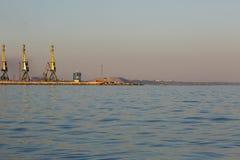 Vele grote kranen silhouetteren in de zeehaven van Azov bij gouden licht van zonsondergang mariupol royalty-vrije stock foto