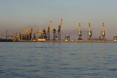 Vele grote kranen silhouetteren in de zeehaven van Azov bij gouden lig royalty-vrije stock afbeelding