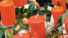 Vele grote multi-colored Kerstmis dikke kaarsen die zich in hulst en sparren bevinden De geest van Kerstmis en nieuw stock videobeelden