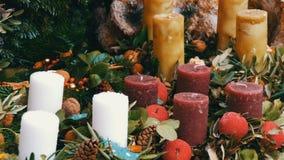 Vele grote multi-colored Kerstmis dikke kaarsen die zich in hulst en sparren bevinden De geest van Kerstmis en nieuw stock footage