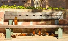 vele grote oranje die flessen bier van glas volledig leeg bij het park toe te schrijven aan somebody wordt gemaakt heeft dronken  royalty-vrije stock afbeelding
