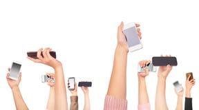 Vele handen die mobiele telefoons houden stock afbeelding