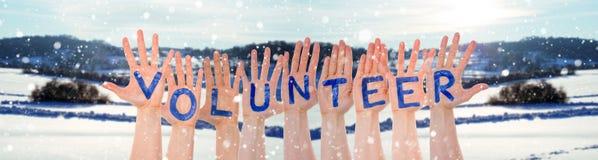 Vele Handen die Word Vrijwilliger, de Winterlandschap als Achtergrond bouwen royalty-vrije stock foto