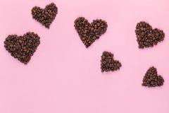 Vele harten van koffiezaden op roze achtergrond stock foto