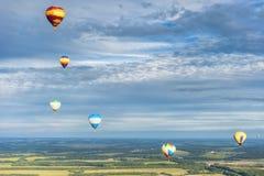 Vele hete luchtballons in de hemel bij blauwe hemel met wolkenachtergrond royalty-vrije stock afbeelding