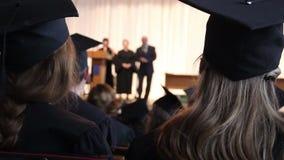 Vele jonge kerels die aan de toespraak van de directeur bij de ceremonie van de universiteitsgraduatie luisteren stock video