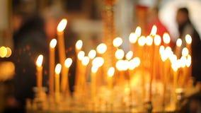 Vele kaarsen die in kerk, brengende mensenvrede en kalmte, gebed branden stock video