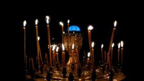 Vele kaarsen die op dark branden stock videobeelden