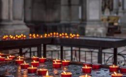 Vele kaarsen in donkere kerk Stock Afbeeldingen