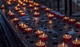 Vele kaarsen in donkere kerk Royalty-vrije Stock Afbeeldingen