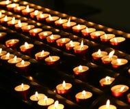 vele kaarsen staken met trillende vlam in de plaats van gebed aan Stock Fotografie