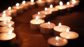 Vele kaarsvlammen die in dark gloeien, leiden tot een geestelijke atmosfeer stock video