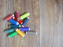 Vele katoenen draden van verschillende regenboogkleuren op houten achtergrondhulpmiddelspoel stock foto's