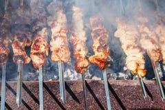 Vele kebabvleespennen die bij de grill voorbereidingen treffen Stock Afbeeldingen