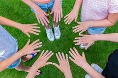 Vele kinderenhanden die in cirkel boven gras toetreden Stock Foto