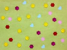 Vele kleine document harten en bloemen op groene achtergrond Royalty-vrije Stock Foto's
