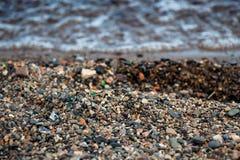 Vele kleine stenen op de kust van een schoon meer Stock Foto's