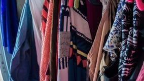 vele kleurrijke kleren die op roze hangers met verschillende kleuren en patronen dicht omhoog foto hangen royalty-vrije stock afbeelding