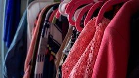 vele kleurrijke kleren die op roze hangers met verschillende kleuren en patronen dicht omhoog foto hangen royalty-vrije stock afbeeldingen