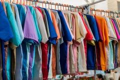 Vele kleurrijke overhemden hangen het verkopen in de markt royalty-vrije stock afbeeldingen