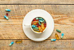 Vele kleurrijke pillen in kop wodden lijst Stock Fotografie
