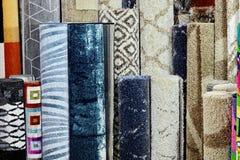 Vele kleurrijke tapijten in de opslag De tapijtbroodjes winkelen Kleurrijke Stoffendecoratie Stock Fotografie