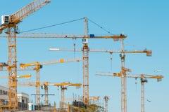 Vele kranen op bouwterrein - bouwkranen op blauwe hemel royalty-vrije stock afbeelding