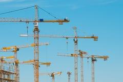 Vele kranen op bouwterrein - bouwkranen op blauwe hemel stock afbeelding
