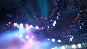Vele lampen en zoeklichten op het overlegstadium Een feestelijk multicolored licht tijdens de prestaties van kunstenaars of rotsm stock video
