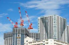 Vele lange gebouwen in aanbouw en kranen onder een blauwe hemel Stock Foto's