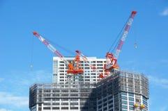 Vele lange gebouwen in aanbouw en kranen onder een blauwe hemel Royalty-vrije Stock Afbeelding