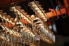 Vele lege glazen voor een wijn die in een bar hangen stock foto