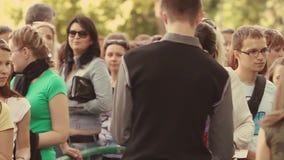 Vele mensen blijven in rij aan ingang bij de zomergebeurtenis veiligheid menigte Volwassene, de jeugd zonnig kaartje stock video