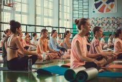 Vele mensen die en praktijk van meditatie in eenvoudige yogaasana ademen maken binnen geschiktheidsclub royalty-vrije stock foto's